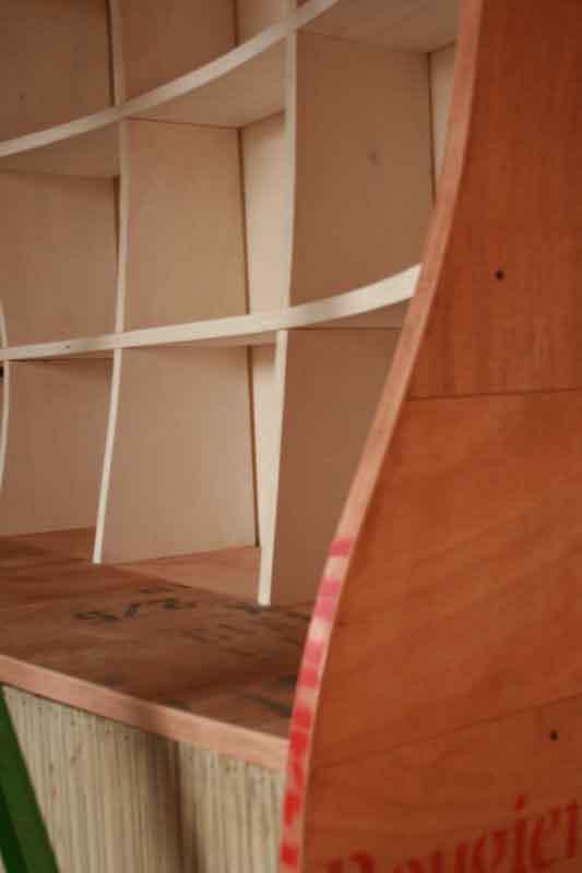 libreria dalle forme curve con legno recuperato
